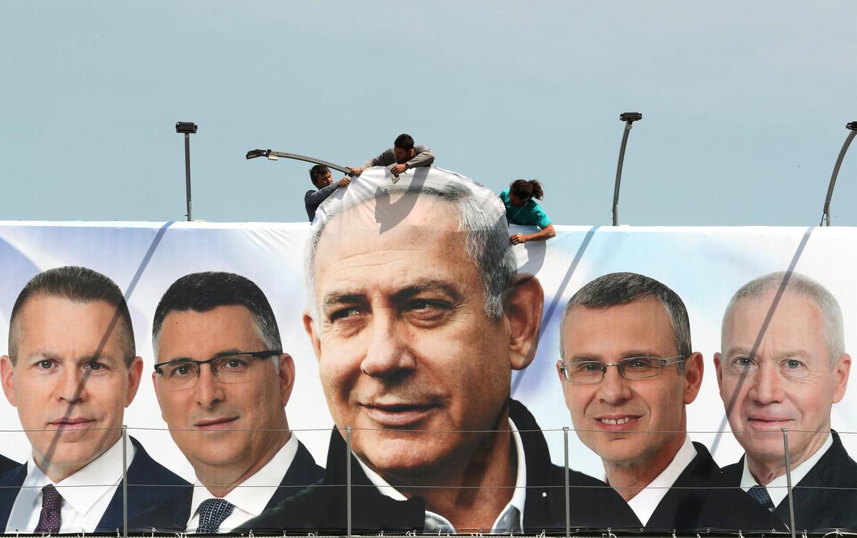 Een verkiezingsfoto van de Minister-president van Israel,  Benjamin Netanyahu (midden), en zijn partijkandidaten, wordt opgehangen in Jeruzalem. Beeld REUTERS