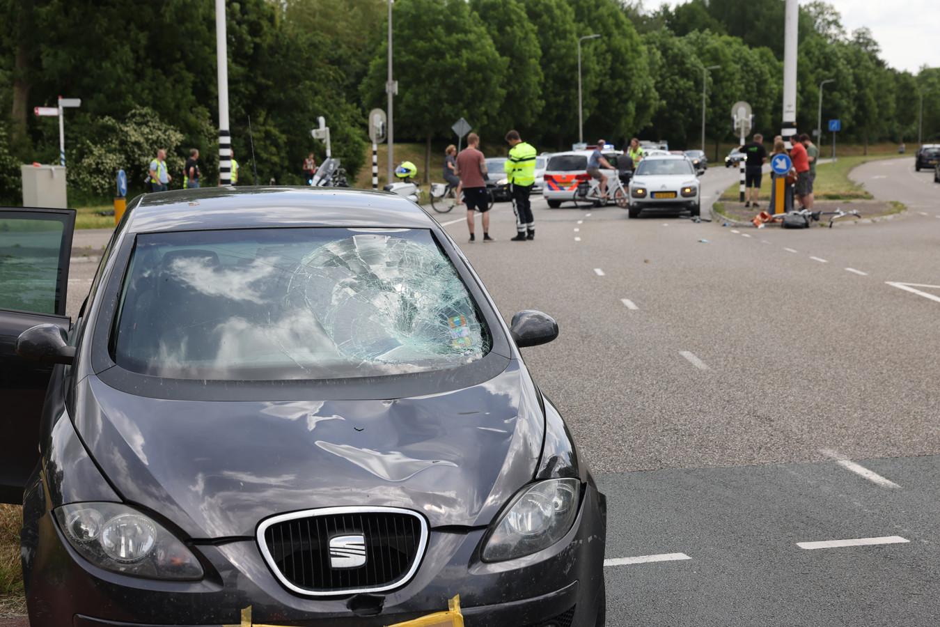 De schade aan de auto, met op de achtergrond de gebroken fiets.