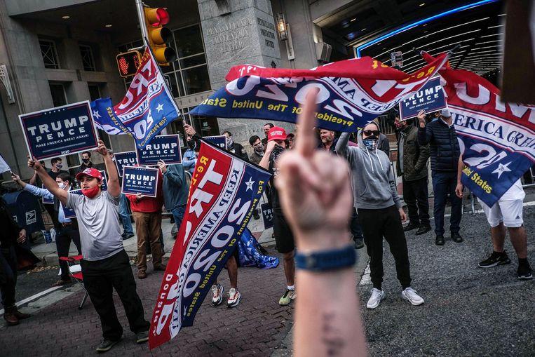 Aanhangers van Trump roepen slogans naar Biden suporters bij het stemmencentrum in Philadelphia. Beeld EPA