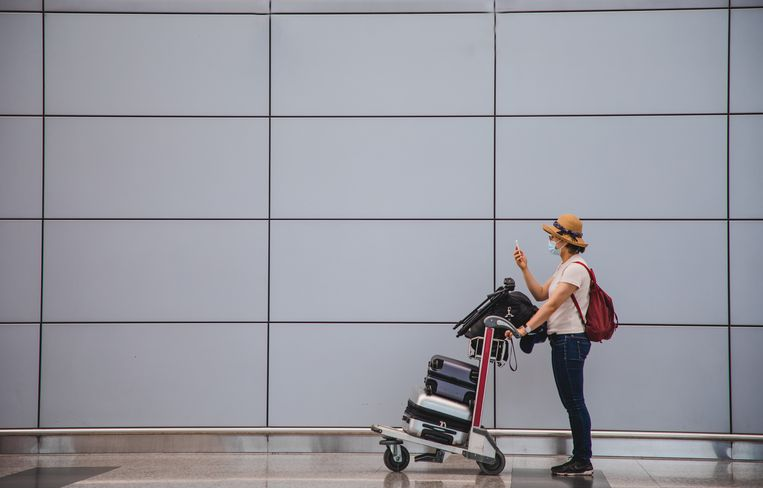 Asian woman with a luggage cart using phone at the airport terminal Beeld Getty Images