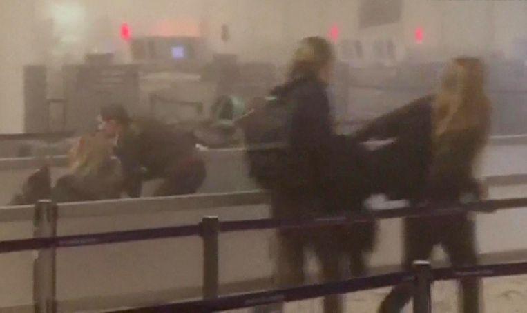 Mensen op het vliegveld Zaventem kort na een explosie. Beeld afp