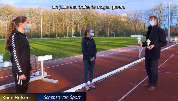 Koen Helsen overhandigt trofeeën aan atleten Emma Van Laer (links) en Heleen Vermeulen (rechts)