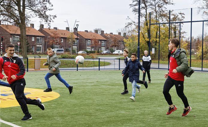 TOP-spelers Delano Ladan (nr 30) en Dean vd Sluijs (nr 12) spelen met jongeren in de Osse Schadewijk.