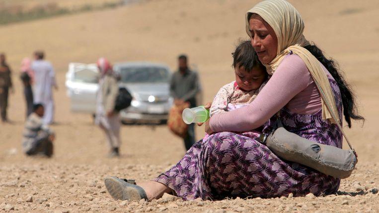 Een vrouw met kind op de vlucht voor IS in augustus van vorig jaar. Beeld REUTERS