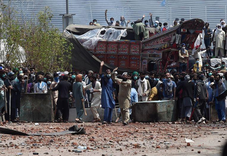 Aanhangers van de verboden radicaal-islamitische partij TLP raken slaags met de politie in Lahore.  Beeld EPA