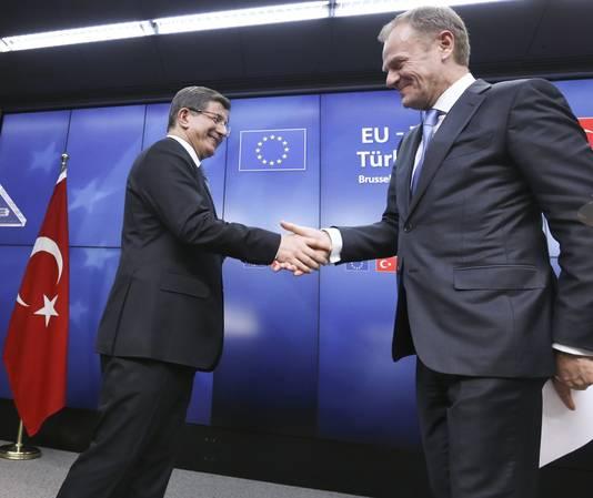 De Turkse premier Davutoglu en EU-president Donald Tusk schudden elkaar de hand na het overleg in Brussel