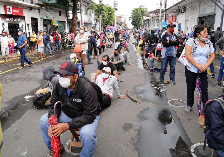 Mensen drommen samen in de rij voor de bank in de Peruaanse stad Iquitos om hun overheidssteun in ontvangst te kunnen nemen.