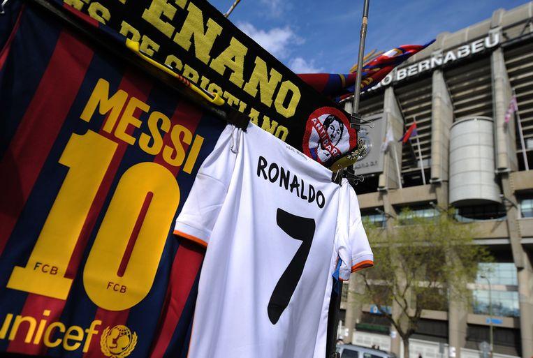 De shirtjes van Lionel Messi en Cristiano Ronaldo zijn uitgestald op zondag bij het stadion Santiago Bernabeu in Madrid Beeld getty