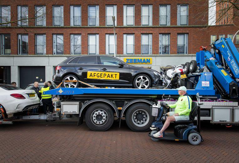 Voertuigen worden door de politie  in beslag genomen tijdens een actie tegen spookbewoning. Bij de actie van politie, OM, de FIOD, Belastingdienst en de gemeente Den Haag zijn zeventien mensen opgepakt. Beeld ANP