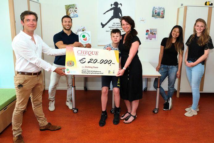 Kim Antonissen en haar zoon Sijmen nemen de cheque voor Stichting Passie in ontvangst.