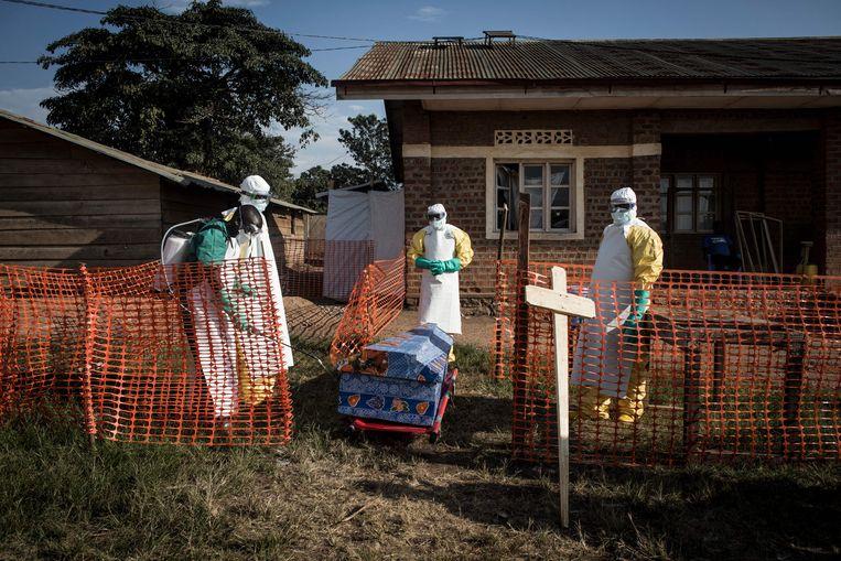 De kist van een overleden ebola-patiënt wordt gedesinfecteerd.  Beeld AFP