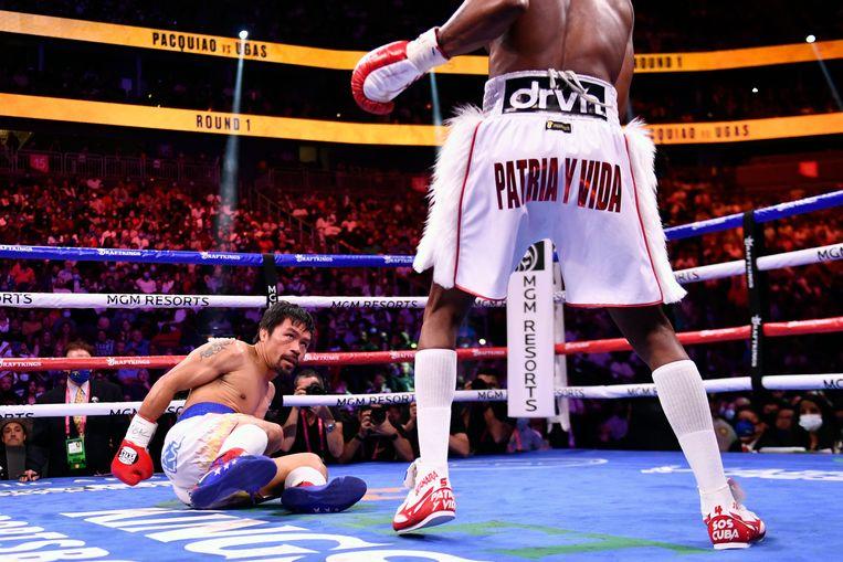 Manny Pacquiao wordt in de eerste ronde naar de grond geslagen door Yordenis Ugas. Beeld AFP