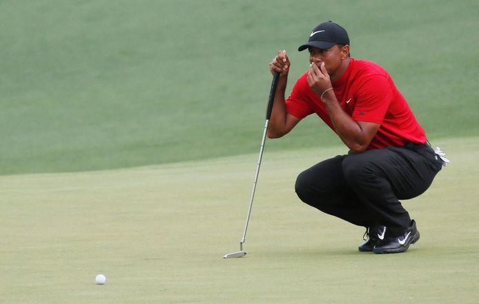 Tiger Woods in rood shirt en zwarte broek.