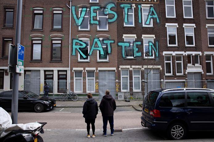Bewoners staan voor een rij panden in de De La Reystraat in de Tweebosbuurt, die op het punt staan gesloopt te worden. Onbekenden spoten er vorige maand als protest deze graffiti op, die Vestia een dag later liet verwijderen.