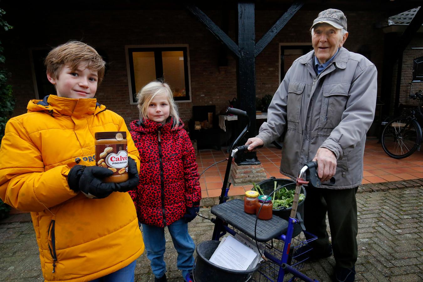 Geert van der Perk met potjes eigengemaakte aardbeienjam op de rollator, naast Noortje en Douwe van Ooijen met de grootste pot pindakaas die ze konden vinden.