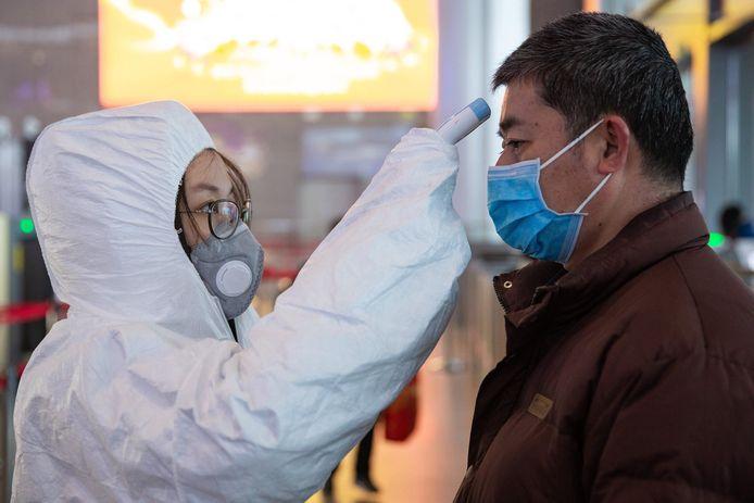 Archiefbeeld: Een gezondheidswerker controleert de temperatuur van een (trein)passagier in Nanjing.