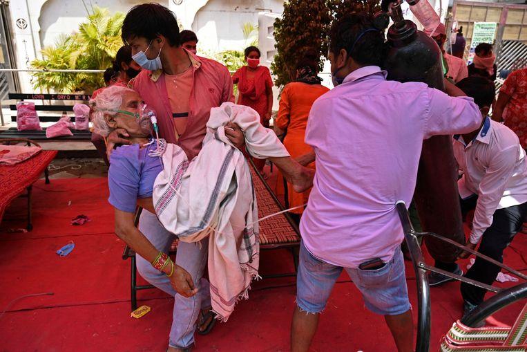 Een familielid helpt een covidpatiënt in een tent waar zuurstof wordt verstrekt in de Indiase stad Ghaziabad.  Beeld AFP