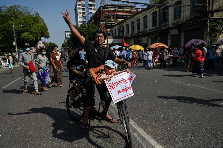 Een demonstrant op de fiets in Yangon.  Beeld AFP