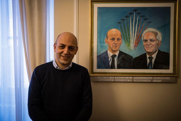Burgemeester Francesco Passerini voor het geschilderd portret van hemzelf en Sergio Mattarella, de president van Italië. Beeld Nicola Zolin