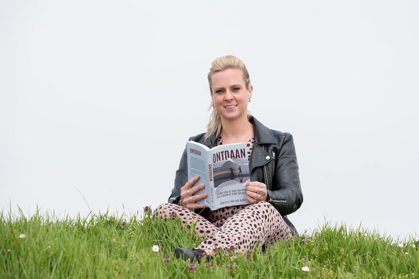 Daniëlle van der Werf met haar boek op een dijk aan de Oosterschelde.