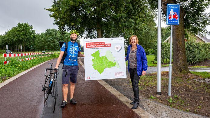 De Nieuwegeinse wethouder Ellie Eggengoor en fietskoerier Sjoerd. De laatste heeft bij provincie en gemeenten in Utrecht handtekeningen opgehaald voor samenwerken aan een regionaal fietsnetwerk.
