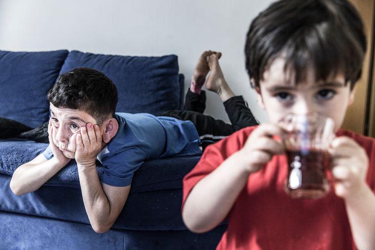 Mohamad en Yusuf hangen voor de breedbeeld-tv.De kelder puilt uit van het speelgoed. Beeld MARLENA WALDTHAUSEN