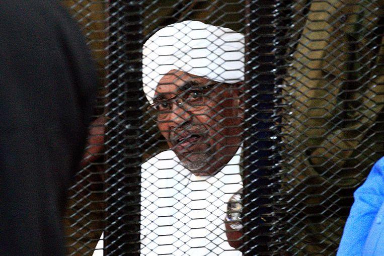 Oud-president Omar al-Bashir in een kooi tijdens zijn rechtszaak in Khartoem. Hij staat terecht wegens corruptie, maar wordt nu uitgeleverd aan het Internationaal Strafhof wegens zijn vermeende betrokkenheid bij mensenrechtenschendingen.  Beeld AFP