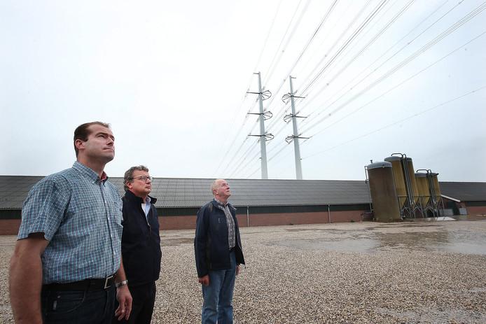 Frank Steenbreker (links), adviseur Fred van Dijk en Franks vader Bennie Steenbreker bij de varkensstallen, met daarboven de hoogspanningsleiding.