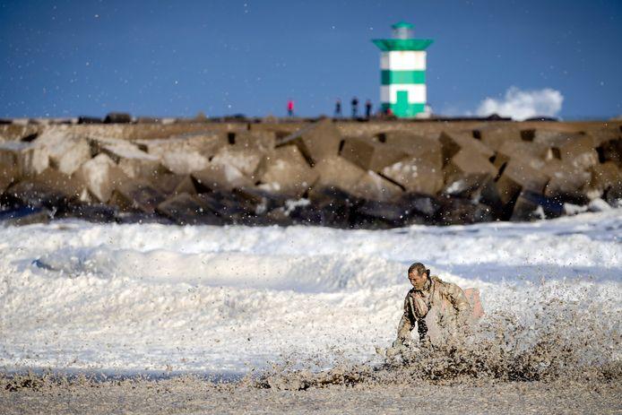 Een medewerker van de KNRM trotseert het opvliegend schuim tijdens de hervatte zoektocht naar de vermiste watersporters bij het Noordelijk Havenhoofd.