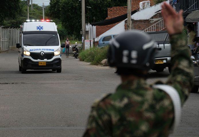 Een soldaat gebaart naar een ambulance die komt aanrijden naar de plek waar de autobom ontplofte.