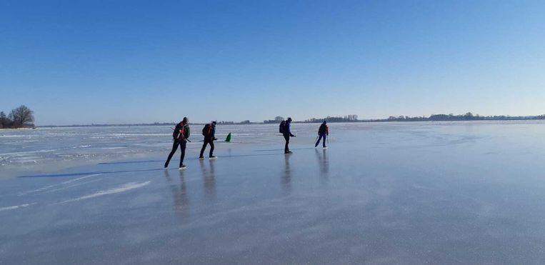 Het Veluwemeer op donderdag 11 februari 2021. Het schaatsgezelschap van Tjerk Gualthérie van Weezel doet een tocht 'op zijn Zweeds', met een gids voorop die de dikte van het ijs meet. Beeld Marijn Giesberts