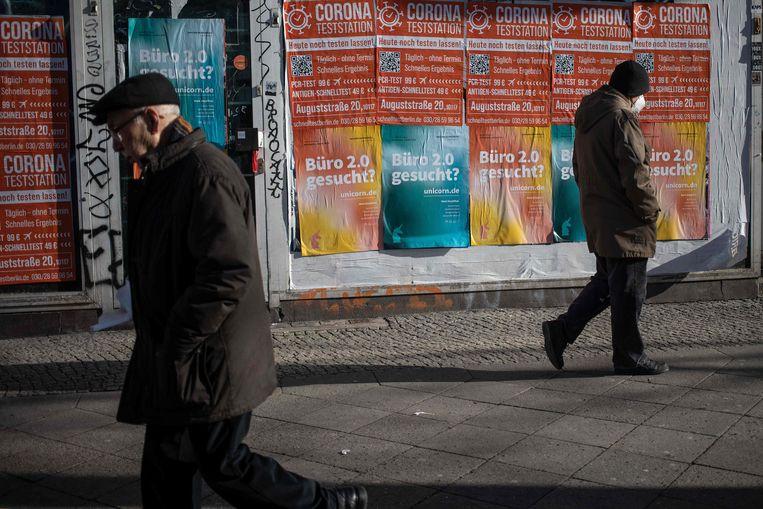 Inwoners van de wijk Kreuzberg in Berlijn lopen langs dichtgetimmerde winkels met posters voor de coronateststraat. Beeld AFP