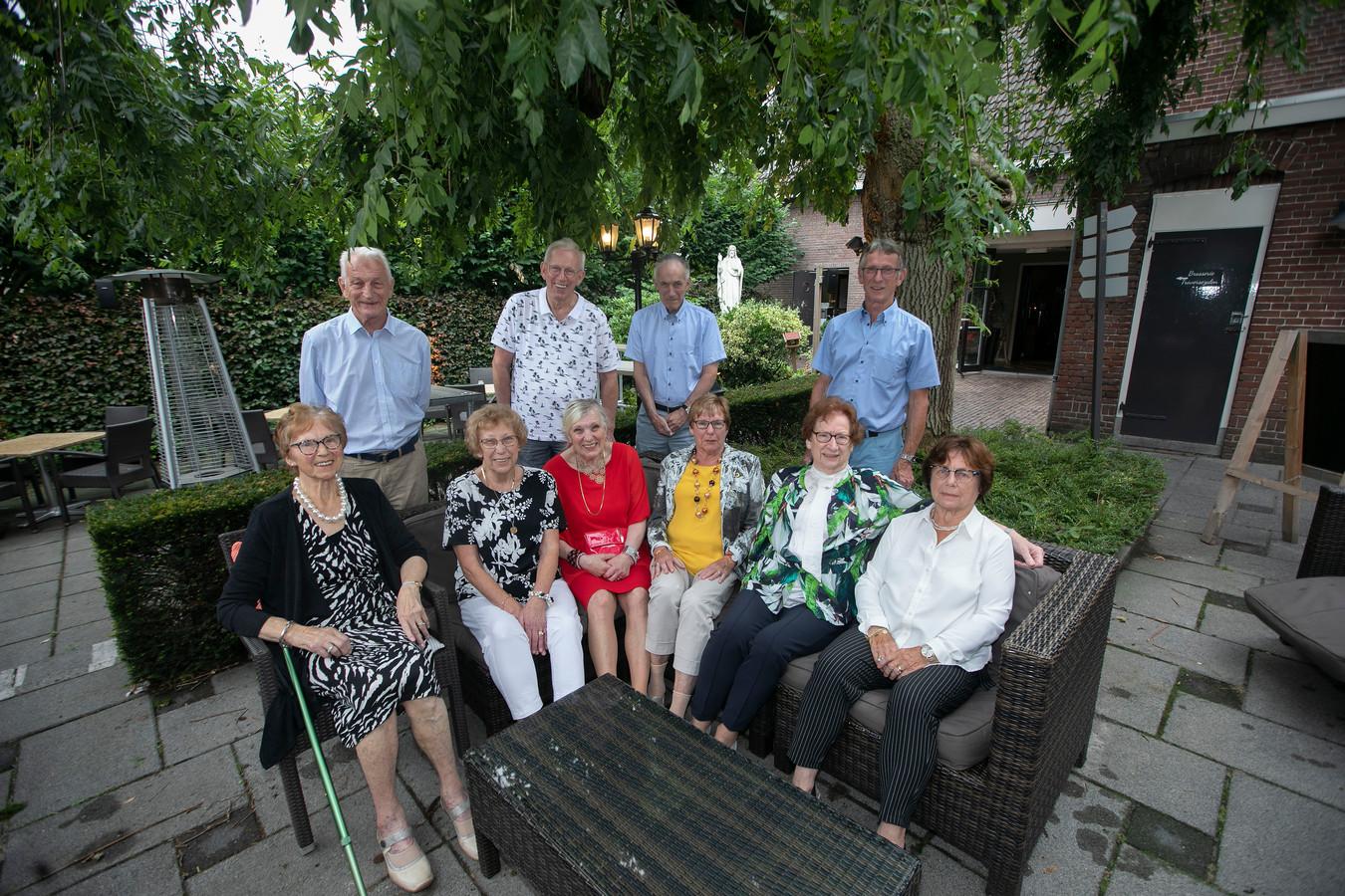 Op de bank (vlnr): Mariet (83), Rieki (79), Gerda (76), Corrie (82), Betsy (85) en Nelly (81). Staand (vlnr): Jos (74), Ad (72), Piet (78) en Henk (71)
