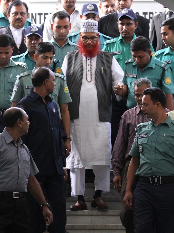 De 71-jarige Delawar Hoessein Sayedee (midden) wordt beschuldigd van misdaden tegen de mensheid, genocide, moord, verkrachting en slavernij.
