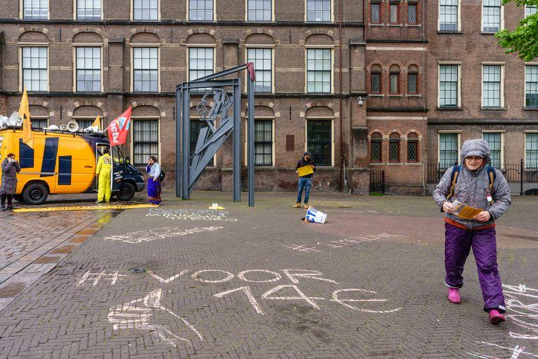 Bij het monument van Willem Drees op de Hofplaats in Den Haag krijten actievoerders de eis van een minimum uurloon van 14 euro op de stoep. Beeld Martijn Beekman