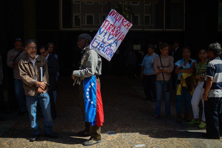 Een man houdt een bord omhoog waarop staat 'dood aan de tirannie, leve de vrijheid' in de buurt van de regeringsgebouwen in Caracas.