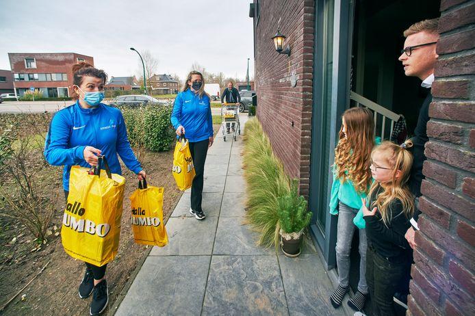 Joyce van Uden (links) en Claudia van der Heiden bezorgen de boodschappen aan de deur bij Dave Eveleens en zijn kinderen Keet en Puck. Op de achtergrond Ivo 't Lam, eigenaar van Fitness4All.