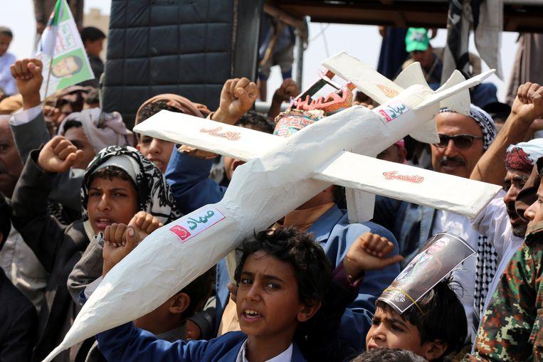 Aanhangers van Houthi-rebellen in Jemen dragen een namaakdrone mee tijdens een demonstratie. Beeld REUTERS