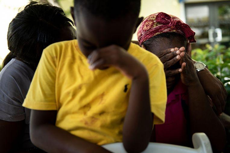 Chrishon Dowkins en zijn oma Catherine Russel rusten uit nadat ze zijn gered en overgebracht naar Nassau. Beeld AFP