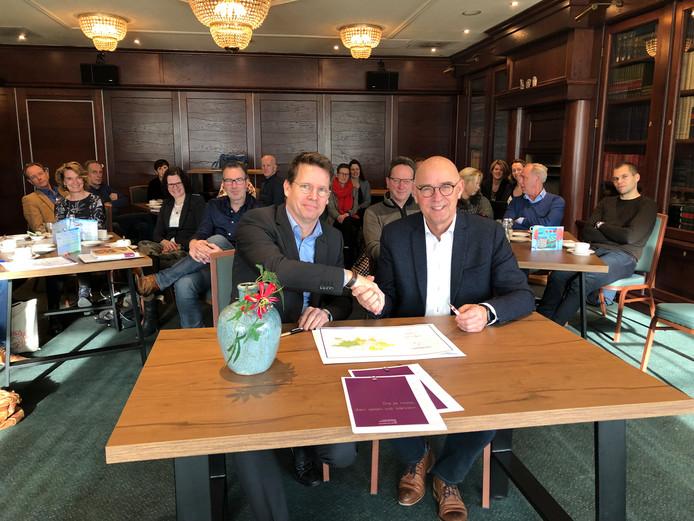 Peter-Paul Rijnkels en Henk Brink (rechts), bestuurders van respectievelijk de stichtingen Welluswijs en Chrono, zetten in zaal Mulder hun handtekeningen onder een intentieovereenkomst om intensiever te gaan samenwerken.