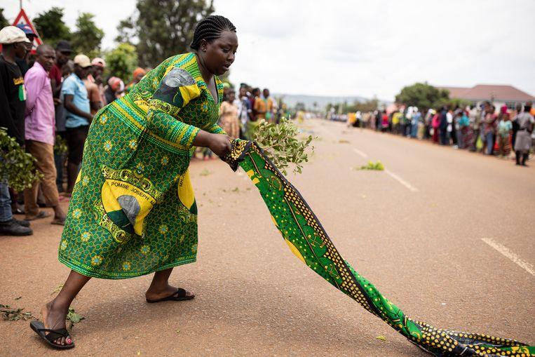 Uit respect legt een vrouw een doek neer, groene bladeren zijn in Tanzania een teken van liefde. Beeld Getty Images