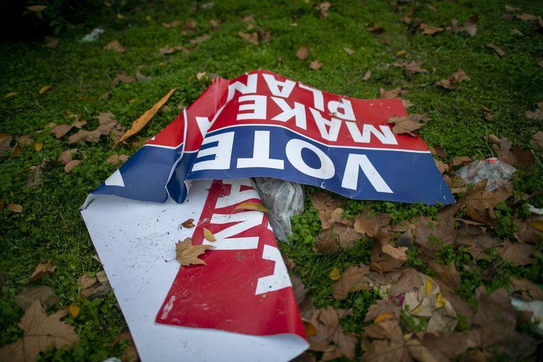 Op een gescheurd bord op de grond staat 'STEMMING MAAK EEN PLAN', aangezien de stembiljetten voor algemene verkiezingen nog steeds in de stad worden opgesteld, zeven dagen nadat het land naar de stembus ging, op 10 november 2020 in Philadelphia, Beeld AFP