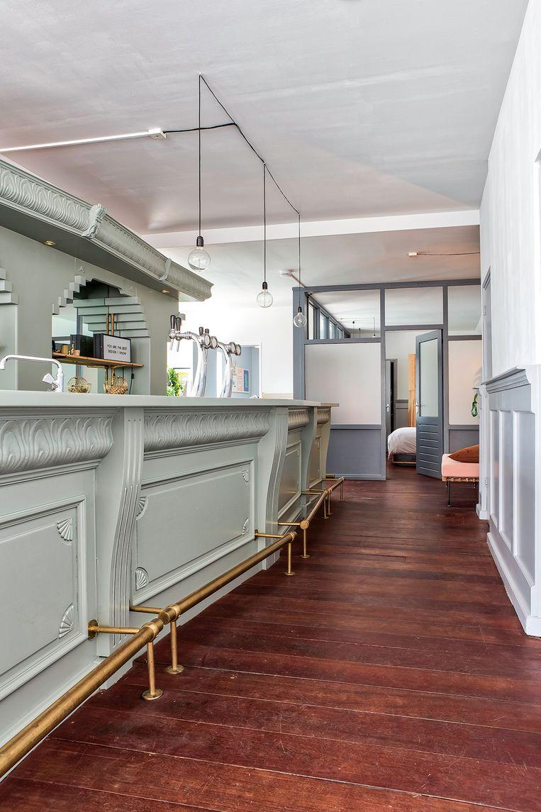 Eyecatcher van de woning: de bar, die ze een opfrisbeurt gaven met een grijsgroene lik verf.  Beeld Henny van Belkom