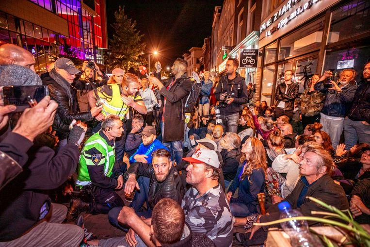 De politie spreekt met demonstranten voor het Utrechtse restaurant WAKU WAKU. Beeld Raymond Rutting / De Volkskrant