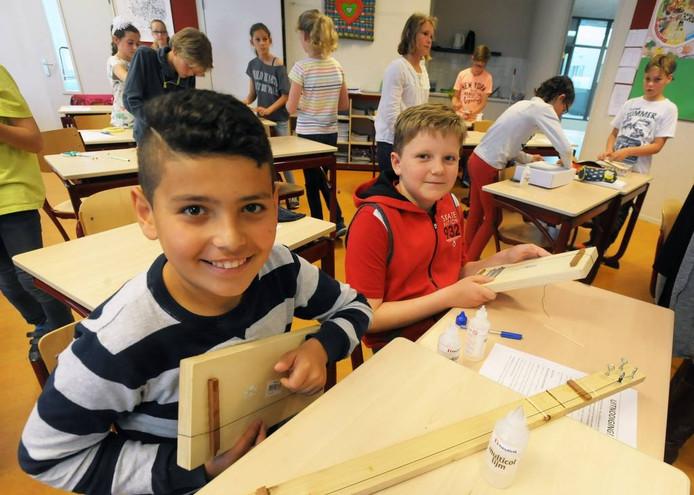 Efekan (links) en Wessel tonen hun geïmproviseerde gitaar in aanbouw.