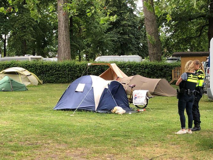 Agenten wachten bij de tent tot specialisten komen voor sporenonderzoek.