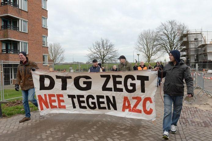 Demonstranten lopen met een spandoek naar het leegstaande Maartenshof in Cuijk.