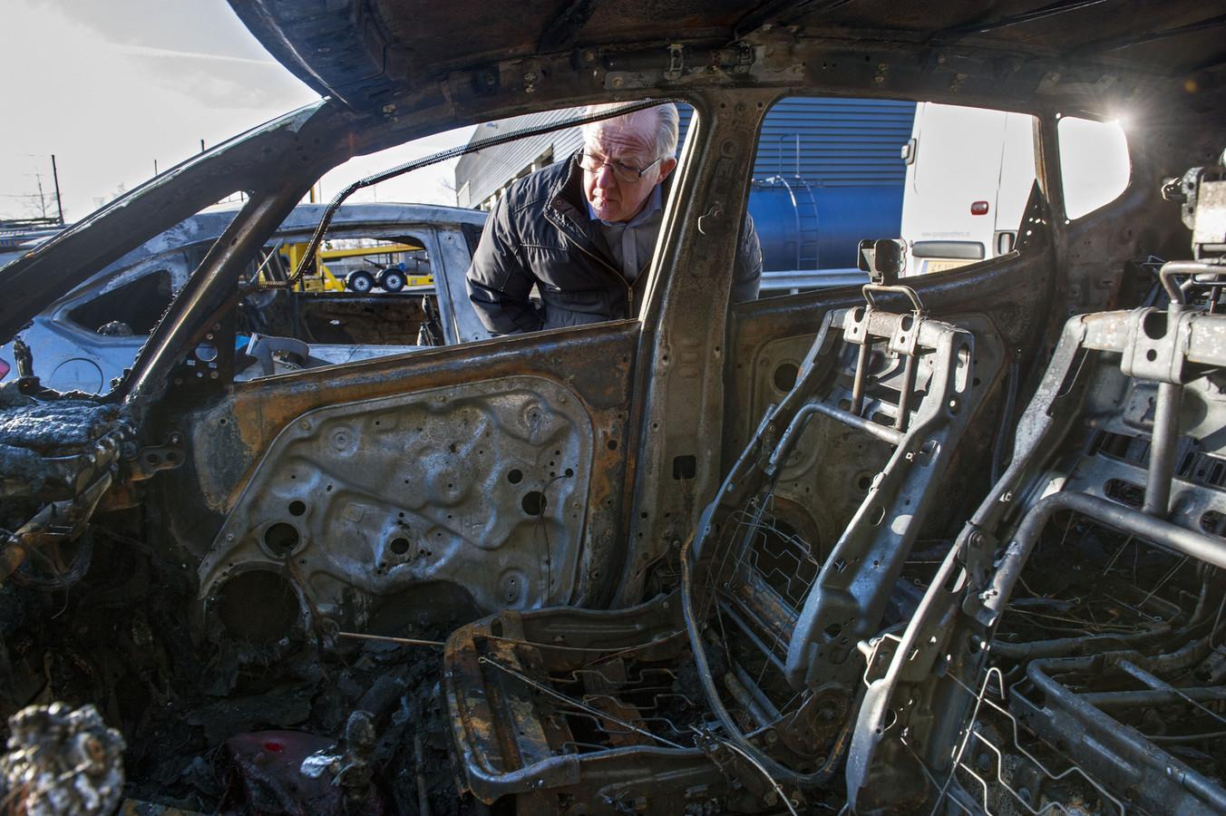 Ton van den Bosch bekijkt de restanten van zijn door vandalen in brand gestoken auto.