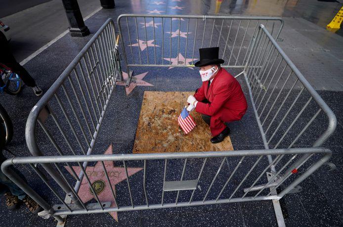Voormalig Beverly Hills-ambassadeur Gregg Donovan zit op 7 november op de Walk of Fame-ster van Donald Trump, nadat democraat Joe Biden de Amerikaanse presidentsverkiezingen won.