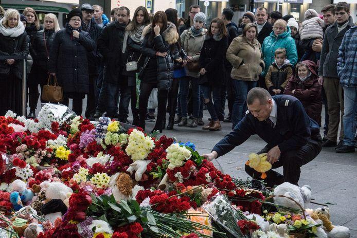 Een piloot legt bloemen neer ter nagedachtenis aan de mensen die in de neergestorte Airbus zaten.